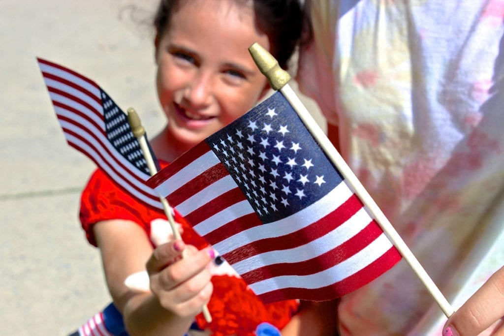children holding small american flags