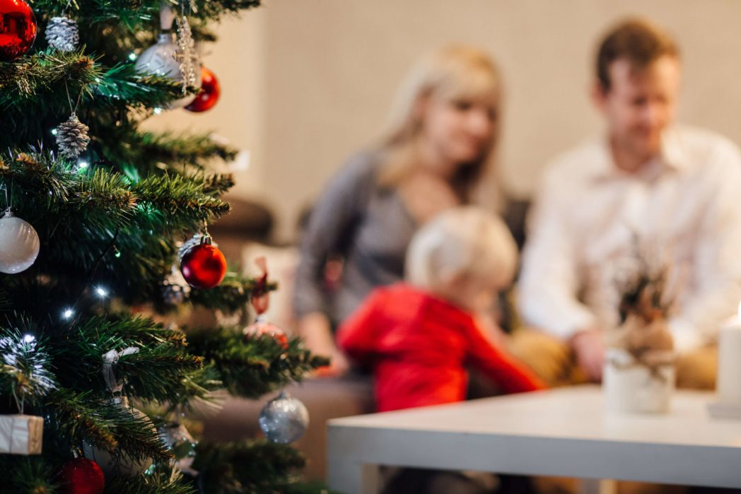 family opening gifts in front of christmas tree