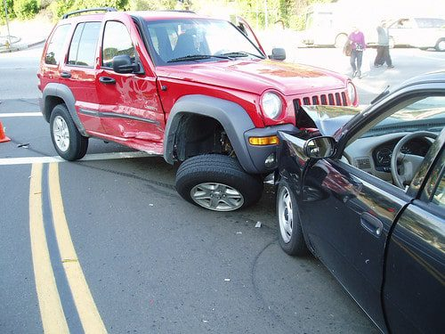 red jeep crashed into the front of a black vehicle