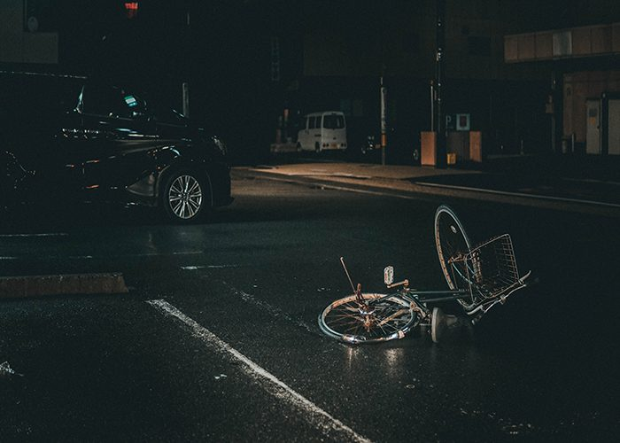 A bicycle lies on a dark street after being hit by a car, an example of an accident calling for the help of a personal injury lawyer.